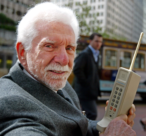 >Martin Cooper holds a Motorola DynaTAC, a 1973 prototype of the first handheld cellular phone